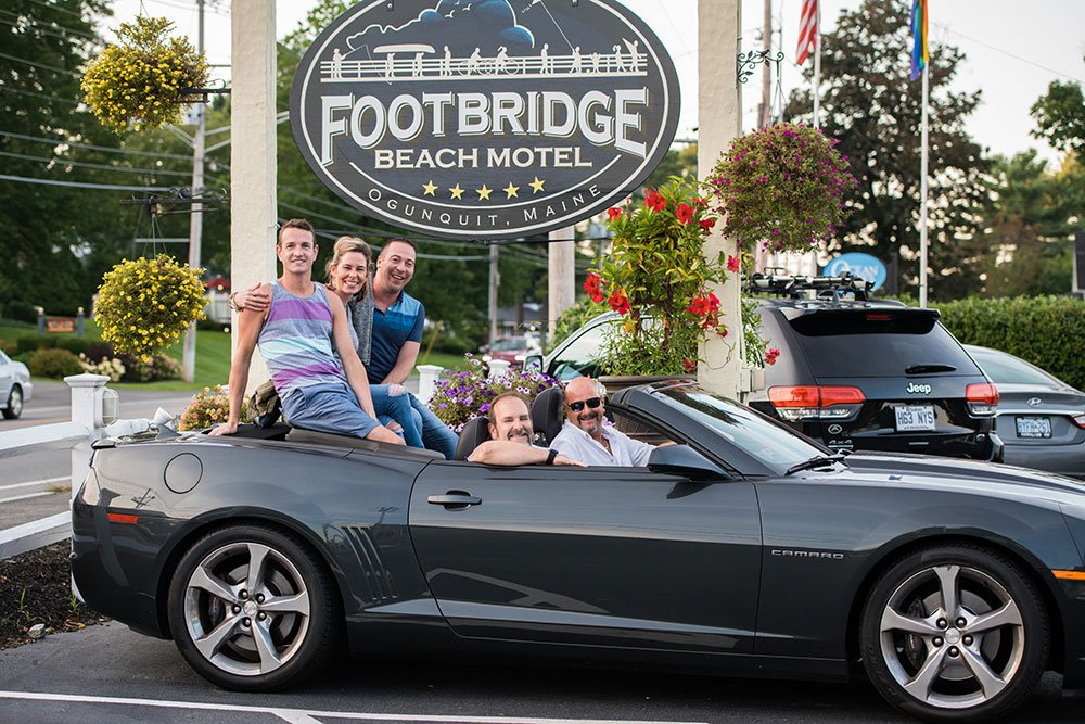 Footbridge team photo in front of the main Footbridge Motel sign