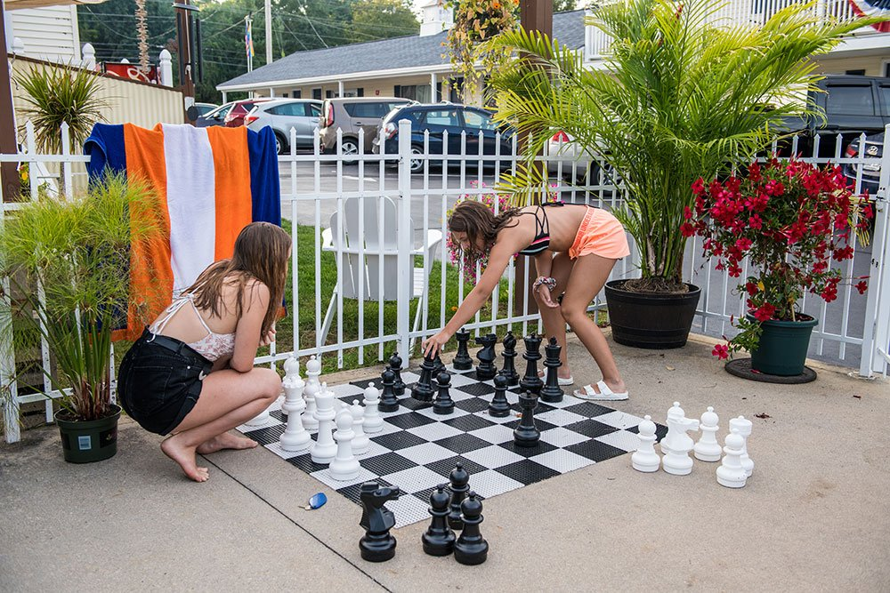 Two teens playing a game of giant chess